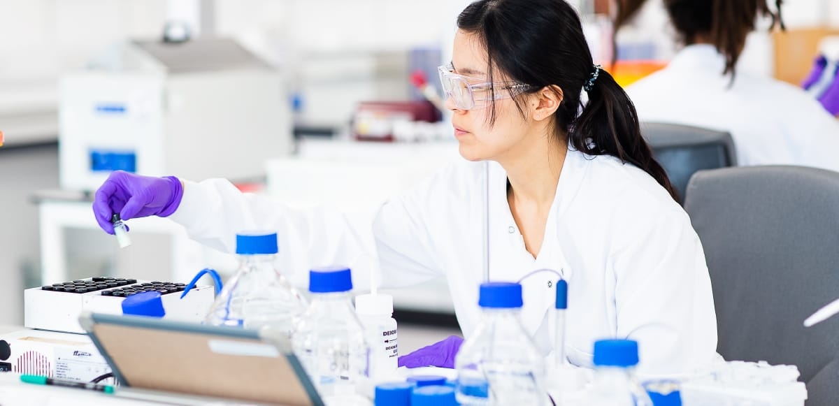 Scientist wearing a lab coat looking at samples in a lab